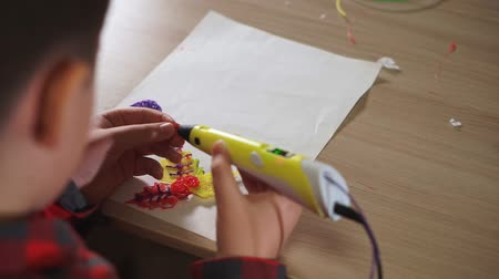 modelagem : Teen boy uses a 3D pen. He sticks together pieces of the figure, creates a plastic flower.