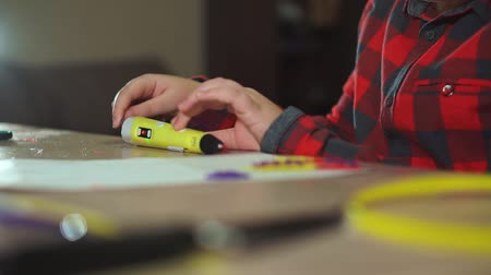 filamento : Teen boy inserts a piece of violet ABS plastic in a 3D pen. He creates a plastic 3D figure.