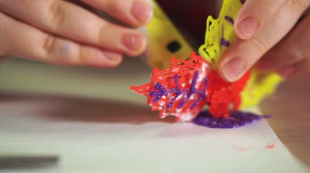 filamento : Close-up of a boys hand create a plastic flower. He uses a 3D pen. Stock Footage