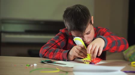 filamento : The boy creates a plastic flower, uses a 3D pen. He learns creatively