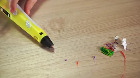 modelagem : On the table is a 3D pen. Near the trash and residues of ABS plastic