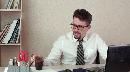 coffe : Man office Manager with a beard and glasses, drinking coffee for a laptop Stock Footage