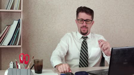 moka : Man office Manager with a beard and glasses, drinking coffee for a laptop Dostupné videozáznamy