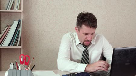 перегружены : Tired Manager working on a laptop. Hes in the office tired and wants to go home