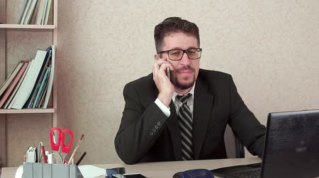 bankier : Office Manager man with beard and glasses talking happily on the smartphone.