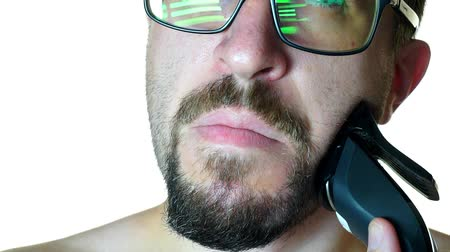bigode : Close-up of a man with glasses shaves off his beard.