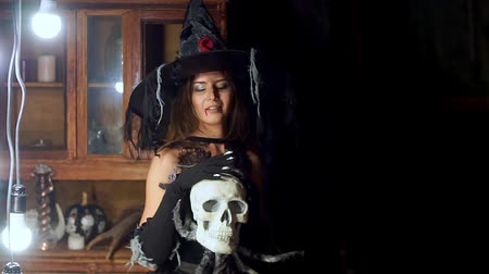 ijesztő : Halloween witch with a staff strokes a skull.