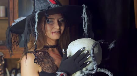 hag : Halloween witch close-up with a staff of a human skull. Sexually smiling