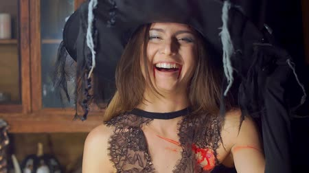 grim : Halloween witch raises her head from under the hat angrily laughing