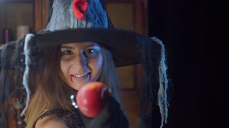 hag : Halloween witch close-up in a hat. Turns to the camera and smiles