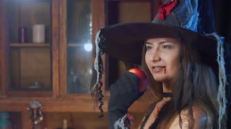 grim : Halloween witch in a hat with a poisonous apple looks dreamily. She dreams Stock Footage
