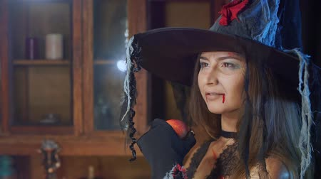 hag : Halloween witch in a hat with a poisonous apple looks dreamily. She dreams Stock Footage