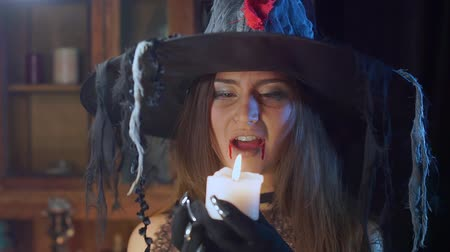 mágico : Halloween witch in a hat holds a candle in his hands. Stock Footage
