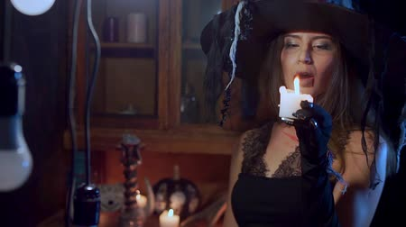 czary : Halloween witch in a hat takes a candle in her hand and blows it out.