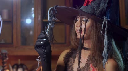 hag : Halloween witch in a hat is looking into the camera. She dreams