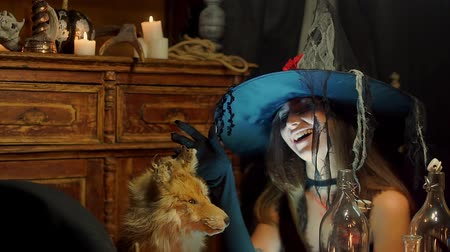 hag : Halloween witch strokes a dead fox and laughs maliciously.