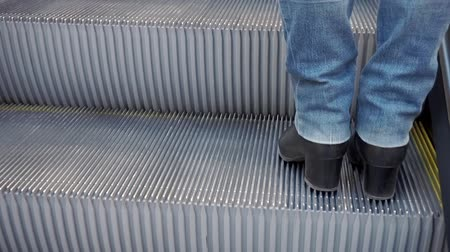 Womens legs in boots and jeans, going up the escalator.