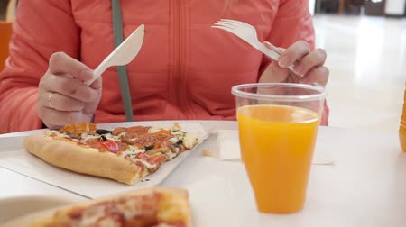 A woman in a cafe eats pizza with a plastic knife and fork.