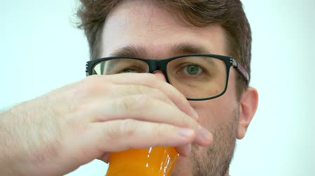 A man in glasses with bristles drinks juice from a plastic cup.