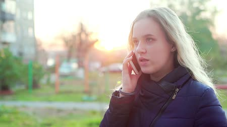 Young attractive girl on the street talking on the phone.