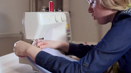 шов : A young woman seamstress works at home, prepares fabric, begins to sew. Sewing machine