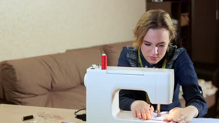 шов : A young seamstress at home at the table working with a white sewing machine. She creates new clothes