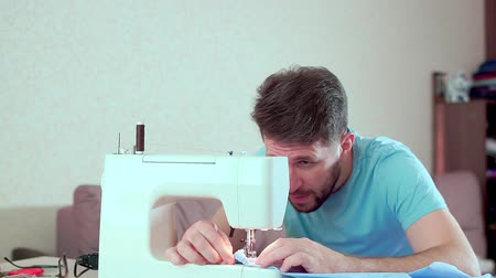 stiksel : A man runs a sewing machine. Workplace at home Stockvideo