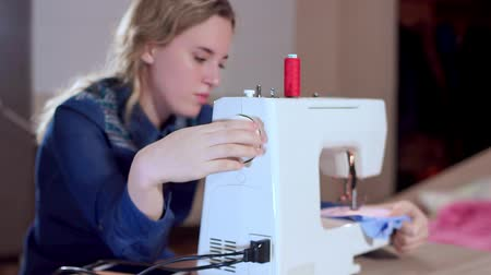 шов : A young seamstress sets up a sewing machine, begins to sew clothes. Focus on the sewing machine, slow motion