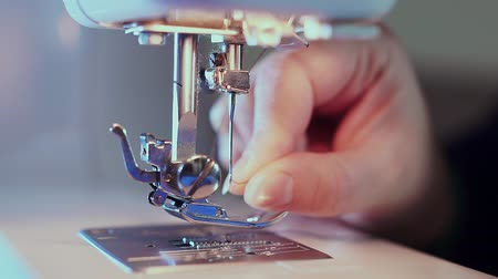 шов : Extra close-up, sewing needle on the machine, the hand of the seamstress inserts the thread. The camera slides forward