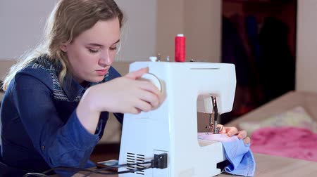 шов : A young seamstress sets up a sewing machine, begins to sew clothes