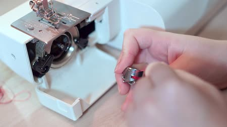 hímzés : Close-up, hands of a seamstress are preparing a bobbin for a sewing machine. Slow motion
