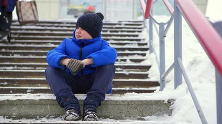 olhando para baixo : Boy teenager in blue down jacket lost in the city. He sits on a cold staircase, looks around.