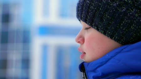 face powder : Close-up boy teenager in blue down jacket. He has steam from his mouth.