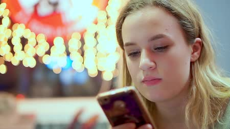 ízléses : Young teen girl read smartphone message. She is having dinner in a cafe. Fast food, evening, on the background of light bulbs, bokeh