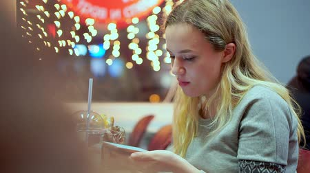 ízléses : Young teen girl writes smartphone message. She is having dinner in a cafe. Fast food, evening, on the background of light bulbs, bokeh Stock mozgókép