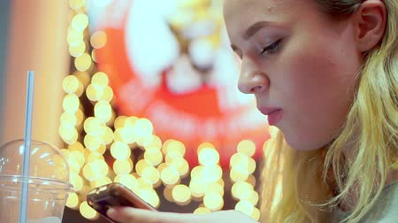 сделанный со вкусом : Young teen girl read smartphone message. She is having dinner in a cafe. Fast food, evening, on the background of light bulbs, bokeh