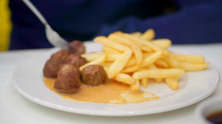 louça : Close-up of a boy eating a meatball. Dipping it in sauce