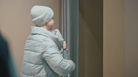 selecionando : Attractive woman trying on a new down jacket in a clothing store. Stock Footage