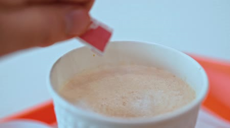 sweetener : Close-up of a cup of coffee. Male hand pours sugar and stir. Fast food