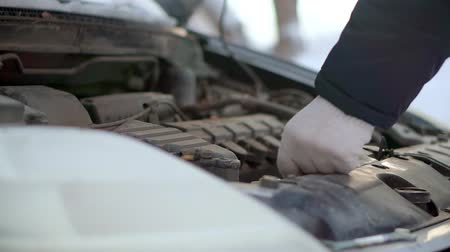 compartimento : A man closes the hood of the motor compartment of his car.