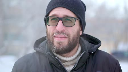 mustache : A man with a beard and glasses looks into the camera. He is outside, very cold Stock Footage