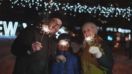 distraído : Family celebrates new year. Father, mother and son laugh and rejoice, waving with Bengal fire. On the street night, winter time Vídeos