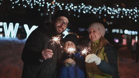 bengália : Family celebrates new year. Father, mother and son laugh and rejoice, in the hands of the Bengal fire. On the street night, winter time Stock mozgókép