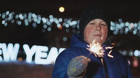 distraído : The boy on the street, New Years Eve. He holds a sparkler and looks at him
