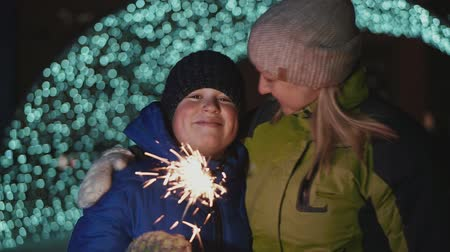 distraído : Boy and mother on the street, New Years Eve. They hold a sparkler and rejoice