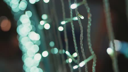 brilhar : Defocused Christmas lights at night outside. Decorations and garlands on the streets of the city.
