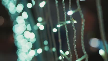 украшать : Defocused Christmas lights at night outside. Decorations and garlands on the streets of the city.