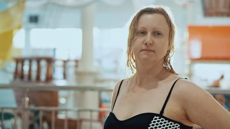 aqua park : A middle aged woman in a swimsuit is looking at park. She has wet hair, she is in aqua park Stock Footage