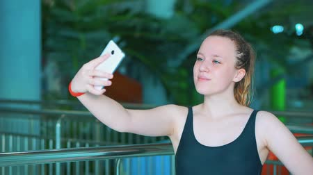 napágy : A young girl in a black bathing suit makes a selfie in a public aqua park.