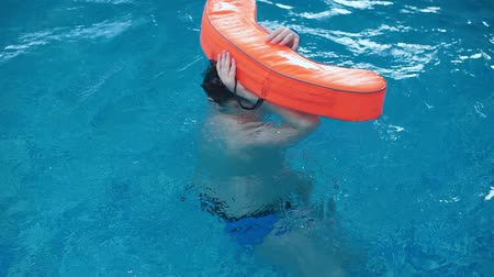 aqua park : A fat boy swims in a pool with a float.
